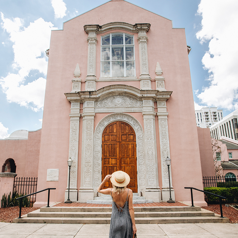 Opal Road Trip - image depicts woman in front of pink building